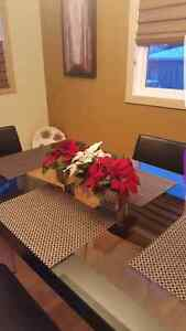 Glass dining room table and 4 leather chairs.