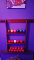 Pool table rack with snooker balls and some que sticks