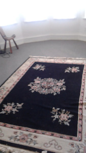 Used black oriental design rug has a cut on one side wool 6'x8'