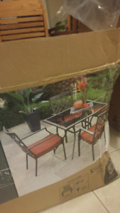 4 brand new patio chairs with red cushions.