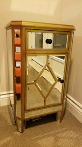 Small cabinet with gold accent and mirror sides