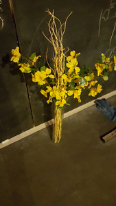 Yellow faux flowers and glass vase