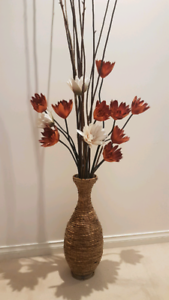 Tall floor vase with decorative sticks and flowers