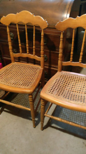 Two antique caned wooden chairs