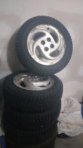 4 like new winter tires on 4 bolt rims. 185/65R15 London Ontario image 1