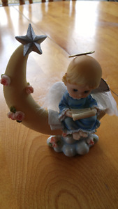 Cherub sitting on the moon figurine