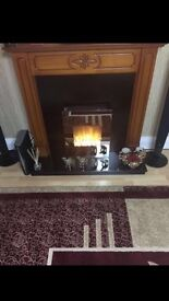 Dark wood fire surround with black hearth and back panel