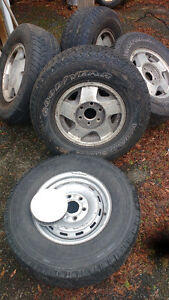 4 stock Chevy rims and 1 spare rim with rubber