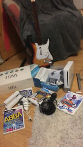 Wii sports console + 5 controllers,nunchuck guitar,mic & games