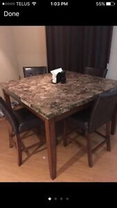 Granite high top dining room table. With chairs
