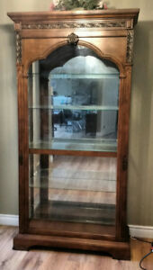 Solid wood ornate lighted display cabinet.
