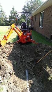 compatct backhoe and operator