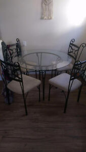 Round glass table with four chairs
