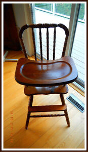 Well-maintained wooden high chair with tray and baby strap