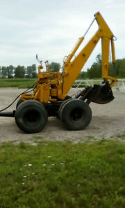 Tow behind backhoe