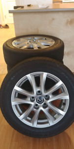 "OEM Mazda 16"" rims with center caps and lugs"