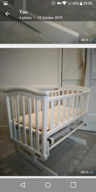 White painted wooden gliding crib