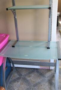 Glass desk with chrome trim and smaller glass shelf