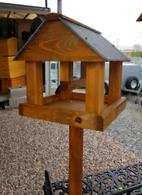 Wooden bird table with nut feeder in centre