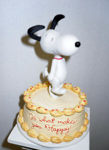 Snoopy Figurine dancing on top of a Cake