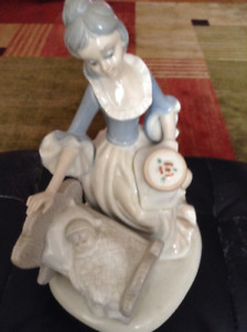 """Tengra 10"""" tall porcelain figurine of a lady withbaby in cradle."""