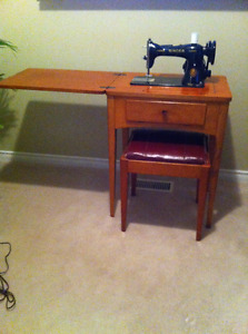 Black Singer Sewing machine with a cabinet and stool