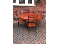 WROUGHT IRON GARDEN CONSERVATORY TABLE AND FOUR CHAIRS.