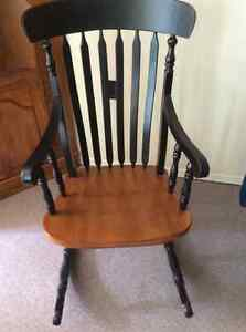 Large sturdy black and wood grain rocking chair with cushion