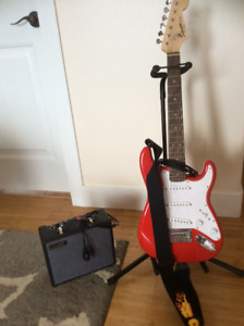 Squier electric guitar with stand, and Sawtooth amp.