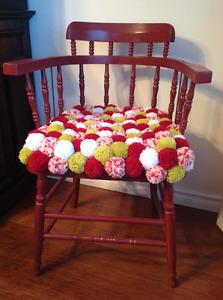 Chaise en bois et coussin en pompons