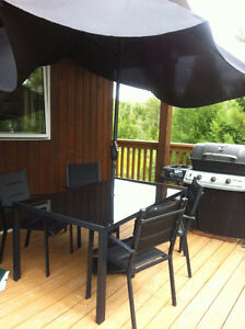 Black glass patio table with umbrella, stand and 4 chairs.