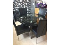 4 black real leather chairs and table.
