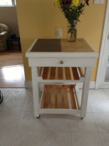 Moveable white island with drawer and cutting board/tile on top.