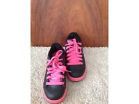 Pink and black sidewalk sports (heelys)