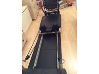 Pilates machine with kick board