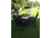 Six seater black table with reclining chairs and black crank parasol