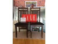 Pair of dark wooden chairs with black leather effect seat pad.