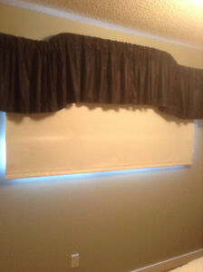 DECORATIVE METAL CURTAIN ROD WITH BLACK VALANCE.