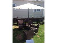 4 BROWN RATTAN GARDEN CHAIRS with CUSHIONS and 1 PARASOL