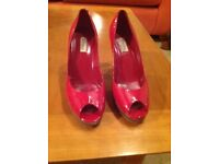 Red patent peep-toe platform shoes by Dune