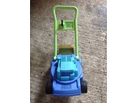 Kids toy lawnmower with moving faux grass