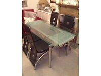 Extending glass dining table with four chairs