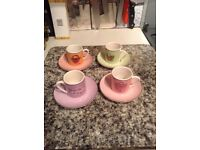 An espresso set of four cups and saucers.