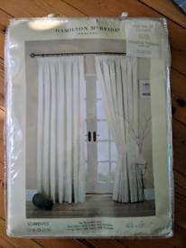 Cream pair of door curtains with tiebacks