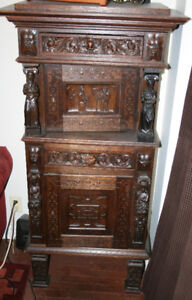 An antique oak armour cabinet with ornate carved decoration