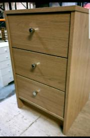 A new stylish oak effect finish three drawer bedside table.