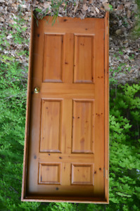 Solid pine door in frame with hardware.