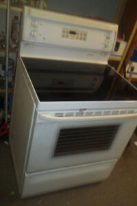 A flat top white stove(electric) and brand new GE stove