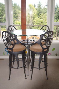 Wrought Iron table with glass top and 4 bar level chairs.