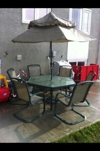 hexagonal glass table with umbrella and 6 chairs